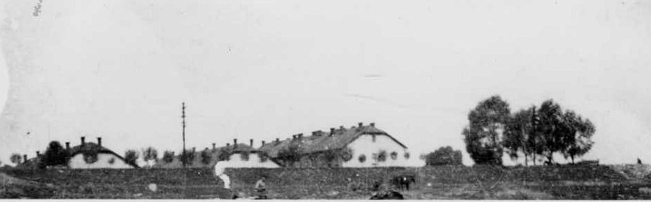 Источник: A-BSMA.  Освенцим. Фрагмент казармы Войска Польского; фотография сделана до войны со стороны реки Сола.  Пока действовал концлагерь, штаб располагался в более высоком здании, а камеры сокамерников - в одноэтажных зданиях (в лагере под номерами 1 и 2, если смотреть справа).  Пока функционировал советский лагерь для военнопленных, на его территории располагались блоки 1 и 2 (пока только одноэтажные). Биркенау, Аушвиц.