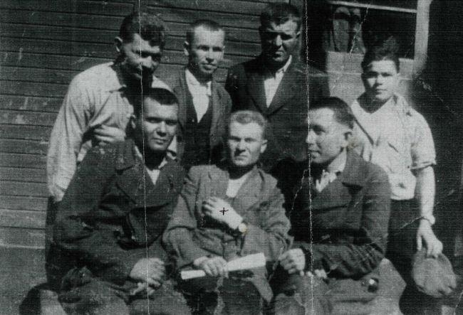 Источник: A-BSMA. Копия фотографии группы заключенных, освобожденных в КЛ Дахау.  В центре (отмечен крестом) сидит Николай Стрелка, который  прибыл в KL Дахау через KL Flossenbürg и был освобожден американской армией 29 апреля 1945 года. Биркенау, Аушвиц.
